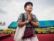 08 JANUARY 2015 - BANGKOK, THAILAND: A woman meditates in front of a statue of a revered Buddhist monk on Sanam Luang. Buddhist in Bangkok have a chance to meditate in front of seven large statues of revered Buddhist monks and worship a hair relic of the Buddha at a series of altars on Sanam Luang near the Grand Palace in Bangkok.    PHOTO BY JACK KURTZ