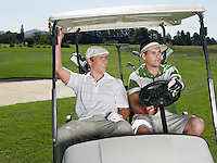 Two young male golfers sitting in cart