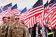 "15 JANUARY 2012 - PHOENIX, AZ:    Soldiers stand in formation while American flags flutter in the wind at the The 161st Air Refueling Wing of the Arizona Air National Guard in Phoenix. About 100 soldiers of A (Alpha) Company of the 422nd Expeditionary Signal Battalion (referred to as ""Alpha 4-2-2"") of the Arizona Army National Guard returned to Arizona on Sunday, Jan. 15, following a nearly year-long deployment to Afghanistan. More than 10,000 Arizona Army and Air National Guard Soldiers and Airmen have been ordered to federal active duty in support of Operations Noble Eagle, Enduring Freedom, Iraqi Freedom, and New Dawn since September 2001. Approximately 200 Arizona National Guard Soldiers and Airmen are still serving on federal active duty overseas.  PHOTO BY JACK KURTZ"