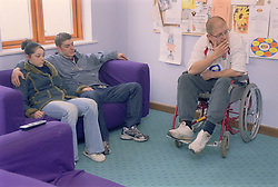 Young couple and man who is a wheelchair user watching television in communal lounge at direct access hostel for homeless and vulnerably housed young people,