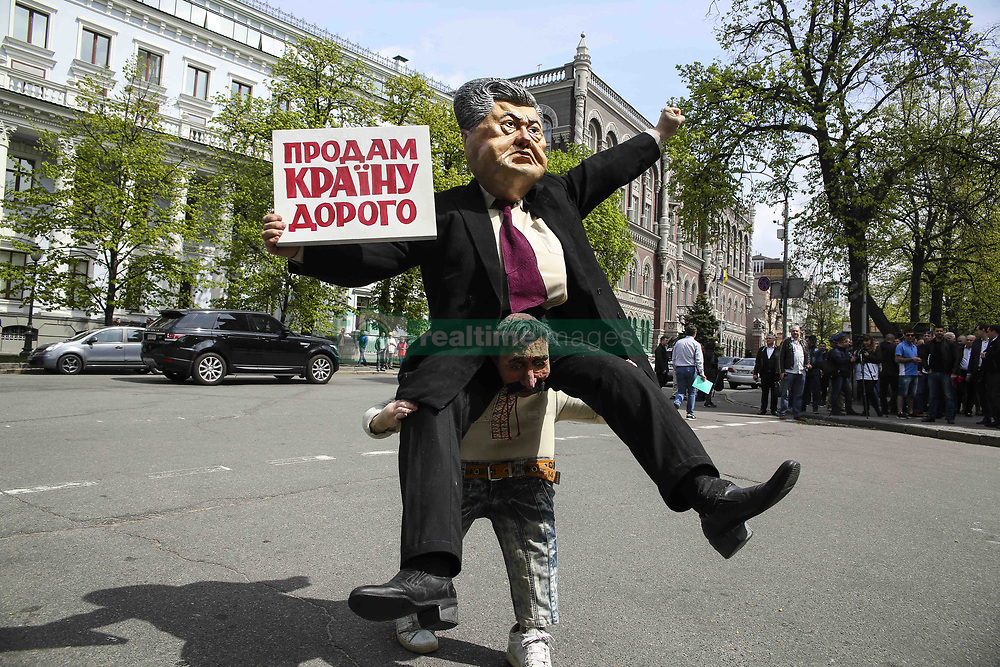 April 25, 2018 - Kiev, Ukraine - A man carries a costume depicting President Petro Poroshenko saddling average Ukrainian citizen and carrying a placard ''The country for sale'' during the performance near the Presidential Administration in Kyiv, Ukraine, April 25,   2018  (Credit Image: © Sergii Kharchenko/NurPhoto via ZUMA Press)