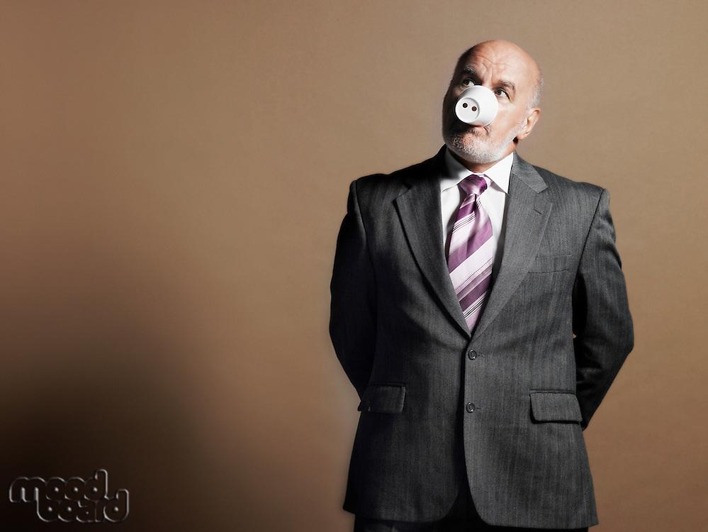 Businessman Wearing Plastic Cup as Pig Snout half length