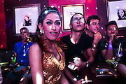 A dragqueen and friends enjoy the show in the gay bar.