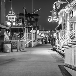 Newport Beach Balboa Fun Zone at night black and white picture with businesses along the boardwalk. The Balboa Fune Zone is a popular attraction in Orange County Southern California. Photo is high resolution. Copyright ⓒ 2017 Paul Velgos with All Rights Reserved.