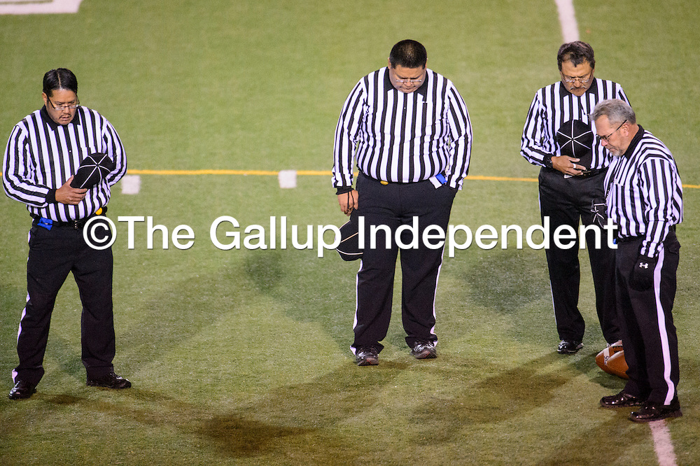 110714       Cable Hoover<br /> <br /> Officials bow their heads during a moment of silence held in honor of former Gallup High School principal Angelo DiPaolo Friday at Public School Stadium.