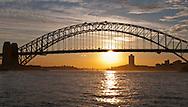The sun sets behind the Sydney Harbor Bridge.