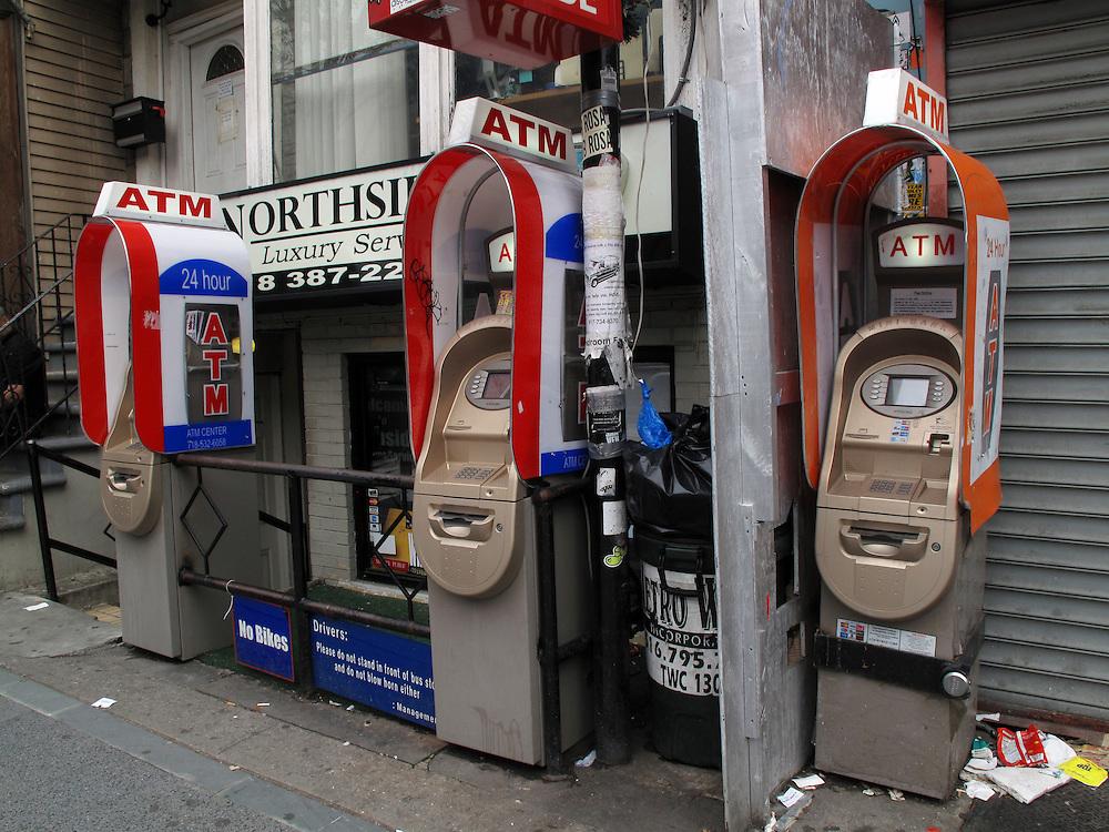 Geldautomaten in New York City Williamsburg Brooklyn USA automated Teller Machines ATM Geld Konsum Handel Kredit.In New York gibt es fast keinen Laden mehr ohne Geldautomat vor oder in dem dem Geschaeft. Zehn bis fuenfzehn Automaten in einer Strasse sind keine Seltenheit. Meist werden sie schnell mit lokaler Werbung und Kleinanzeigen beklebt. Immer mehr werden gestohlen und nach Entleerung in diversen Gewaessern entsorgt. Die Diebe rammen die ATMs oft rueckwaerts mit einem Kleinlastwagen aus der Verankerung und transportieren sie dann ab..There is hardly any store in New York without an ATM. Ten or fifteen machines on one block is common. Most are quickly covered with local advertising and personal notes. ATM theft is on the rise, pickup trucks are used to steal whole machines which are later dumped in rivers and lakes around New York.