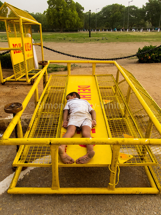 28th May 2015, New Delhi. A boy sleeps on a police barrier in New Delhi, India on the 28th May 2015<br /> <br /> Sleeping in the outdoors is common in Asia due to a warmer climate and the fact that personal privacy for sleep is not so culturally ingrained as it is in the West. New Delhi (where most of these images were taken) is a harsh city both in climate and environment and for those working long hours, often in hard manual labour, sleep and rest is something fallen into when exhaustion overwhelms, no matter the place or circumstance. Then there are the homeless, in Delhi figures for them from Government and NGO sources vary wildly from 25,000 to more than 10 times that. Others public sleepers may simply be travellers having a siesta along the way.<br />  <br /> <br /> PHOTOGRAPH BY AND COPYRIGHT OF SIMON DE TREY-WHITE, photographer in Delhi<br /> <br /> + 91 98103 99809<br /> email: simon@simondetreywhite.com