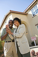 Portrait of middle-aged couple with key to new home