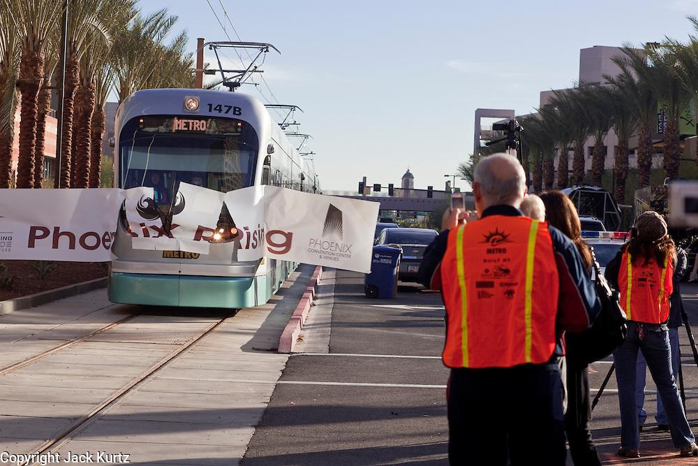 "27 DECEMBER 2008 -- PHOENIX, AZ: The first official light rail train to arrive in Phoenix burst through a banner that read ""Phoenix Rising."" Metro Light Rail started running Saturday, Dec. 28. The light rail line is 20 miles long and cost $1.4 billion dollars. PHOTO BY JACK KURTZ"