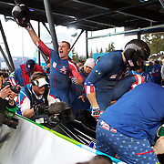 "Winter Olympics, Vancouver, 2010.Curtis Tomasevicz (centre) celebrates as the USA-1 team of Steven Holcomb, Justin Olsen, Steve Mesler and Curtis Tomasezicz win the Gold Medal in the Bobsleigh Four-man at The Whistler Sliding Centre, Whistler, during the Vancouver Winter Olympics. 27th February 2010. Photo Tim Clayton..'BOB'..Images from the Four-man Bobsleigh Competition. Winter Olympics, Vancouver 2010..History was made at the Whistler Sliding Centre when the USA four-man bobsleigh team, led by Steven Holcomb took the Gold. The first time since 1948, a gap of 62 years, since the USA have won an Olympic Bobsleigh gold and they did it with their sleigh named ""Night Train""...The four days of practice and competition show the tension, nervousness and preparation as the teams of hardened men cope with the challenge of traveling at average speeds of over 150 km an hour. Indeed, five teams had already pulled out of the event before the opening heats because of track complexity, speed and fear, and on the final day, another four teams did not start after six crashes in the first two heats...Teams warm up behind the start complex, warming muscles in the cold in preparation for the explosive start. Many teams prepare in silence, mentally preparing themselves as they wait at the top of the run, in the bobsleigh sheds and the loading areas for their turn. When it's time to slide each team performs it's own starting ritual, followed by the much practiced start out of the blocks for just over four seconds, the teams are then in the hands of the accomplished drivers as they hurtle down the track for just over fifty seconds...Spectators clamber for the best position on track to see the sleighs for a split second, many unsuccessfully try to capture the moments on camera, The rumble of the sleigh is heard then the crowds gasp as it hurtles past in a blur...The American foursome of  Steven Holcomb, Justin Olsen, Steve Mesler and Curtis Tomasevicz finished with a pooled four-heat tim"