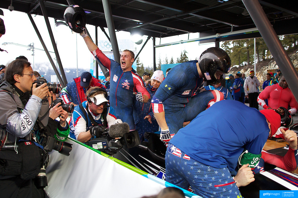 """Winter Olympics, Vancouver, 2010.Curtis Tomasevicz (centre) celebrates as the USA-1 team of Steven Holcomb, Justin Olsen, Steve Mesler and Curtis Tomasezicz win the Gold Medal in the Bobsleigh Four-man at The Whistler Sliding Centre, Whistler, during the Vancouver Winter Olympics. 27th February 2010. Photo Tim Clayton..'BOB'..Images from the Four-man Bobsleigh Competition. Winter Olympics, Vancouver 2010..History was made at the Whistler Sliding Centre when the USA four-man bobsleigh team, led by Steven Holcomb took the Gold. The first time since 1948, a gap of 62 years, since the USA have won an Olympic Bobsleigh gold and they did it with their sleigh named """"Night Train""""...The four days of practice and competition show the tension, nervousness and preparation as the teams of hardened men cope with the challenge of traveling at average speeds of over 150 km an hour. Indeed, five teams had already pulled out of the event before the opening heats because of track complexity, speed and fear, and on the final day, another four teams did not start after six crashes in the first two heats...Teams warm up behind the start complex, warming muscles in the cold in preparation for the explosive start. Many teams prepare in silence, mentally preparing themselves as they wait at the top of the run, in the bobsleigh sheds and the loading areas for their turn. When it's time to slide each team performs it's own starting ritual, followed by the much practiced start out of the blocks for just over four seconds, the teams are then in the hands of the accomplished drivers as they hurtle down the track for just over fifty seconds...Spectators clamber for the best position on track to see the sleighs for a split second, many unsuccessfully try to capture the moments on camera, The rumble of the sleigh is heard then the crowds gasp as it hurtles past in a blur...The American foursome of  Steven Holcomb, Justin Olsen, Steve Mesler and Curtis Tomasevicz finished with a pooled four-heat tim"""