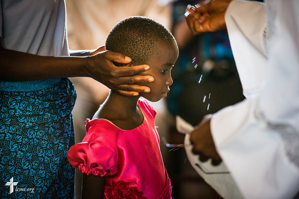 A child is baptized by the the Rev. Davis Wowa, executive chairman of the Confessional Lutheran Church–Malawi Synod, during worship on Sunday, Sept. 27, 2015, at a parish in Chingale, Malawi. LCMS Communications/Erik M. Lunsford