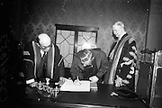 23/04/1964<br /> 04/23/1964<br /> 23 April 1964<br /> Honorary Degrees conferred at the National University of Ireland, Iveagh House, Dublin. <br /> Picture shows Lieut.-General Michael J. Costello (Degree LL.D.), General Manager Irish Sugar Co., signing the register after the ceremony watched by President Eamon de Valera (right), Chancellor of N.U.I. and Dr. Seamus Wilmot, Registar of the University.