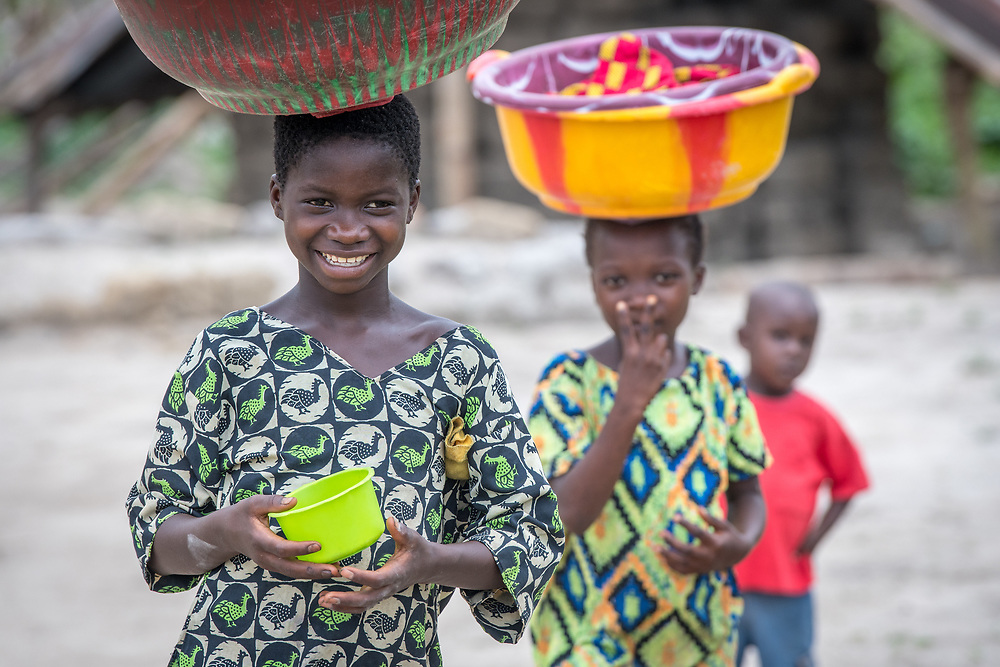 Two young girls carry colorful buckets on their heads in Ganta Liberia