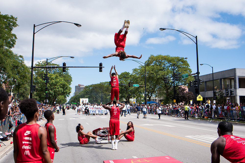 A member of the Jesse White Tumblers performs a flip over two fellow tumblers near 45th Street.