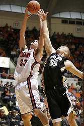 Jason Cain (33) grabs one of his 10 rebounds in the game, beating Wake Forest's Kyle Visser (55) to the ball.  The Wahoos beat the Decons 75-73.