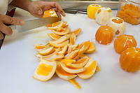 Close-up of hands slicing oranges with knife