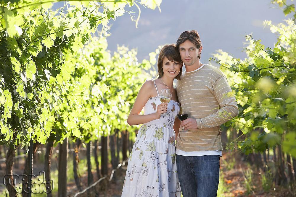 Young couple with wine glasses in vineyard