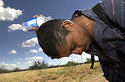 A man who crossed illegally into the U.S. from Mexico on to the Buenos Aries Wildlife Refuge in the Sonoran Desert cools off with water west of Arivaca, Arizona, USA.  The man was separated from his group after running from border patrol during the night.  He wandered alone in the desert after becoming disoriented.
