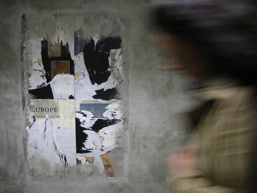 A figure moving infront of torn posters on a wall