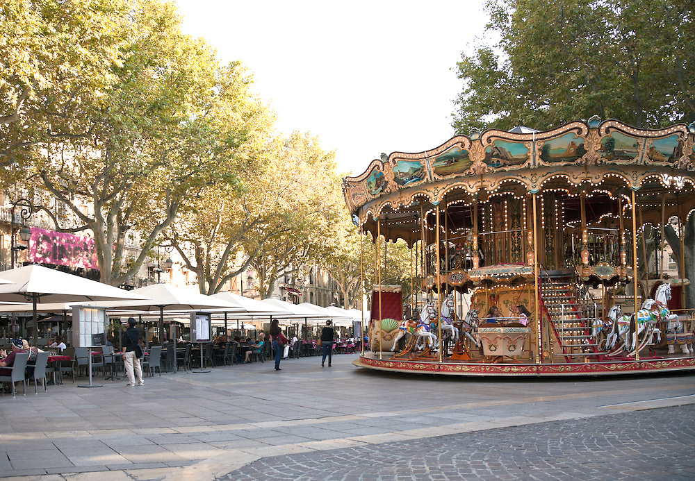 While strollers check out the day's offerings at the cafes, the carousel adds a touch of fun to the Place de L'Horloge in Avignon, France.