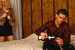 man on a bed in a hotel pouring champagne while a woman in the background gets undressed