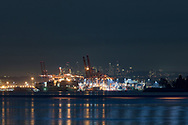 The Port of Vancouver and the waters of Burrard Inlet after sunset. Photographed in the evening from Ambleside Park along the shoreline in West Vancouver, British Columbia, Canada. Background towers are in the city of  Burnaby.