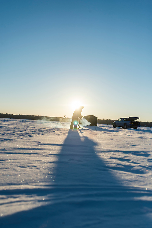 An ice fisherman drills a hole through 18 inches of ice while fishing on Little Bay de Noc near Gladstone and Escanaba, Michigan.