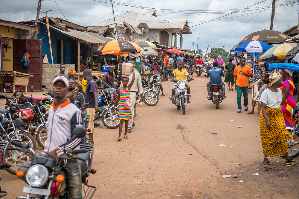 Men gather with their motorcycles in Ganta, Liberia