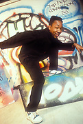 MC Mello posing in front of graffiti wall, U.K, 1989.