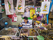 08 JANUARY 2015 - BANGKOK, THAILAND:  A vendor in the Bangkok amulet market repairs a customer's amulet. Hundreds of vendors sell amulet and Buddhist religious paraphernalia to people in the Amulet Market, an area north of the Grand Palace near Wat Maharat in Bangkok.            PHOTO BY JACK KURTZ