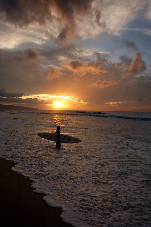 Surfer at sunset on Oahu's famous north shore, Hawaii