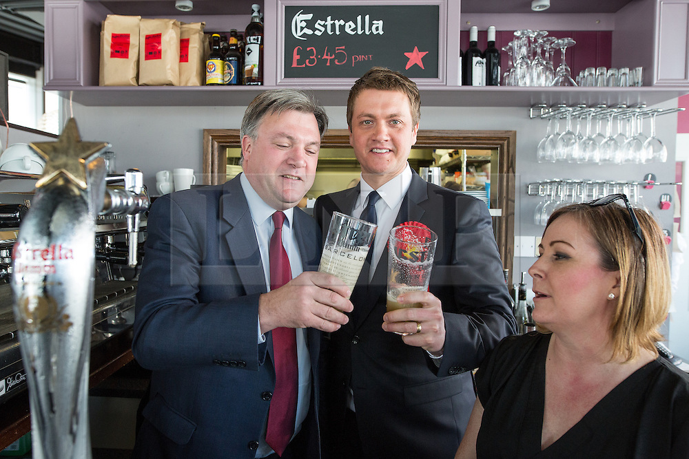 © Licensed to London News Pictures . 11/04/2015 . Bury , UK . Labour Shadow Ed Balls (l) and James Frith (c) , Labour candidate for Bury North , at a campaign stop with the owner of Barista coffee shop (r) at The Rock , Bury in Greater Manchester , UK . The pair met parents and discussed family finances . Photo credit : Joel Goodman/LNP