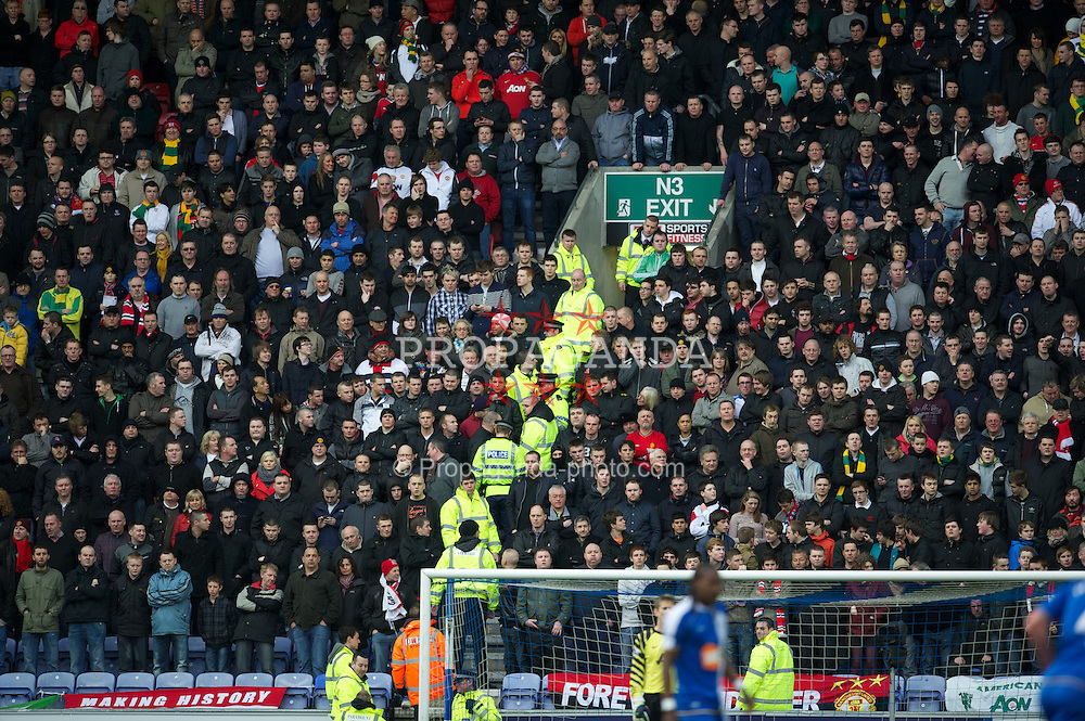 WIGAN, ENGLAND - Saturday, February 26, 2011: Stewards and police try to prevent Manchester United supporters from standing in the stairways during the Premiership match against Wigan Athletic at the DW Stadium. (Photo by David Rawcliffe/Propaganda)