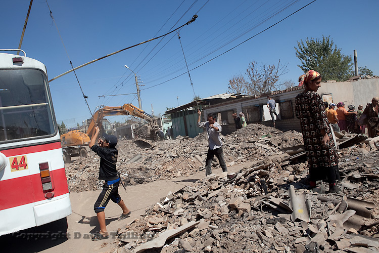 Women scavange through the rubble on a main street in Osh. Aid workers worry the debris is full of asbestos dust.