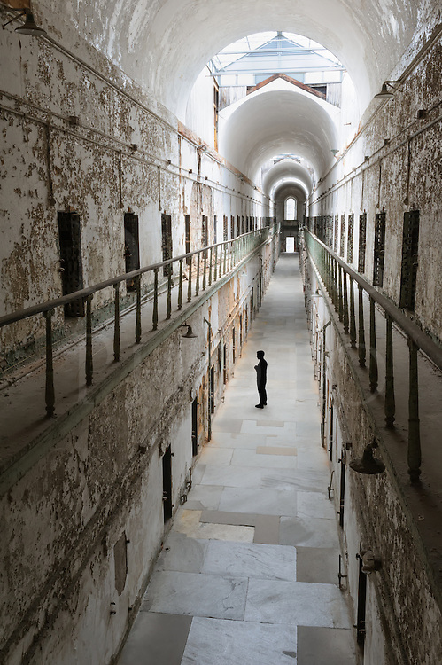 Prison cell block from high angle view with one unrecognizable prisoner in silhouette, Eastern State Penitentiary, Philadelphia, PA, USA.