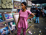06 AUGUST 2017 - MENGWI, BALI, INDONESIA: A woman walks past the paintings and art work she's selling in the Bringkit Market in Mengwi, about 30 minutes from Denpasar. Bringkit Market is famous on Bali for its Sunday livestock and poultry market. Hundreds of the small Bali cows are bought and sold there every week. Bali's local markets are open on an every three day rotating schedule because venders travel from town to town. Before modern refrigeration and convenience stores became common place on Bali, markets were thriving community gatherings. Fewer people shop at markets now as more and more consumers go to convenience stores and more families have refrigerators.     PHOTO BY JACK KURTZ