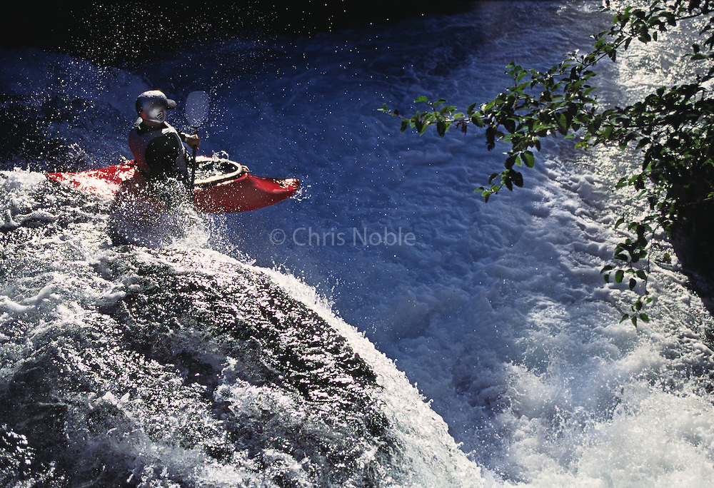 A kayaker negotiates a waterfall while running Davis Creek on Alaska's Seward Penninsula.