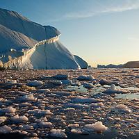 Greenland, Ilulissat, Midnight sun lights massive iceberg calved from Jakobshavn Glacier grounded at mouth of Disko Bay on summer evening