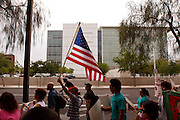 04/25/12-  Andy DeLisle.A protestor holds a US flag in the March for Justice against SB 1070 on Wednesday April, 25 2012 in Phoenix, AZ.