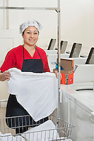 Portrait of a happy woman wearing uniform holding clothes with washing machines in background