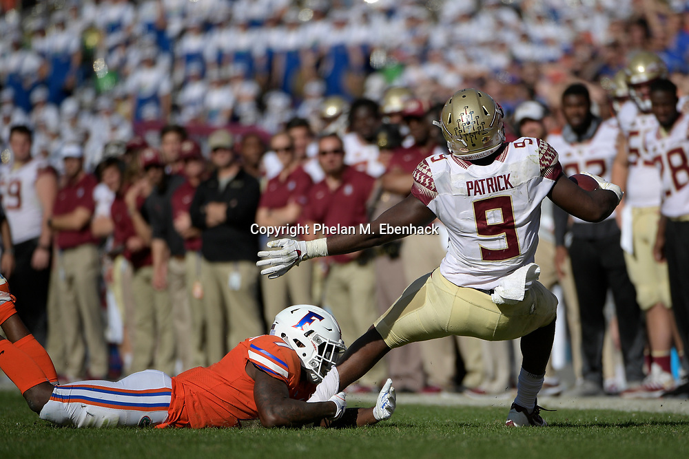 Florida State running back Jacques Patrick (9) is tackled by Florida defensive back Duke Dawson (7) after rushing for yardage during the second half of an NCAA college football game Saturday, Nov. 25, 2017, in Gainesville, Fla. FSU won 38-22. (Photo by Phelan M. Ebenhack)