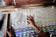 Aklima Khatun works on her rug at the Mornia Kik Rug Factory in Doani Villlage, Haragach Upazila, Rangpur, Bangladesh on 19th September 2011 where she works alongside 25 rural village women making rugs for German textile discounter Kik. Over 400 women have been economically empowered through the CARE Bangladesh WONDER Project that was completed recently. The WONDER Project's goals were to create sustainable income and employment opportunities for extremely poor women by training them in rug production for export. The women now earn about 4000 Bangladeshi Taka per month. The WONDER Project has now moved into a new phase that focusses on general healthcare, workplace safety and nutritional training and awareness programs. Photo by Suzanne Lee for The Guardian