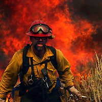 Nevada Division of Forestry firefighter Greg Jackson (cq) sets backfire in an attempt to contain the Waterfall fire Thursday, July 15, 2004 near Carson City, Nevada. Flames from the aggressive blaze ravished homes and quickly spread over 10,000 acres of land.<br /><br />The Sacramento Bee / Carl Costas