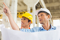Male architect explaining building plan to colleague at construction site