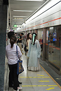 Chinese women in traditional Chinese clothes boarding a subway train. Photographed in Chengdu, Sichuan, China