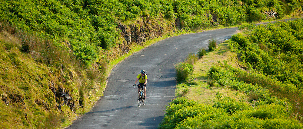 Tourist cycling along country road through Cumbrian mountains in Lake District National Park, UK
