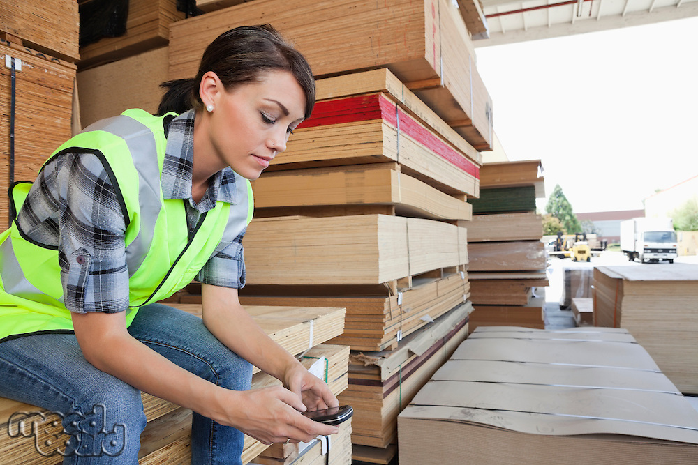 Female industrial worker using cell phone while sitting on stack of wooden planks