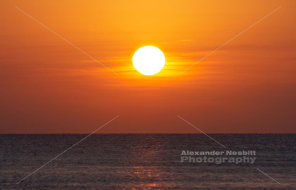 Belize, Central America - Centered sunset over calm ocean